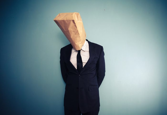 sad and ashamed businessman with bag over head